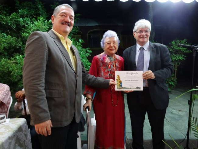 Myriam Brindeiro recebe diploma das mãos de Alexandre Santos. A saudação foi de Geraldo Ferraz (à esquerda da foto).